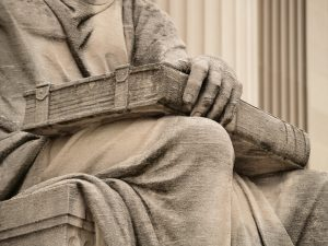 Statue Possessively Holding a Book